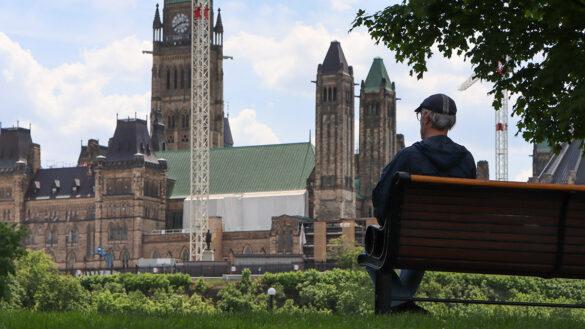 A man sits on a park bench overlook Parliament Hill.