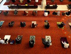 Photo taken from above, people sit on prayer mats six feet apart.