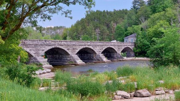 A bridge with five stone arches spans rapids.