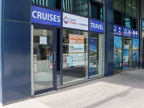 """A travel agency with a sign in the window that reads """"space for sublease""""."""