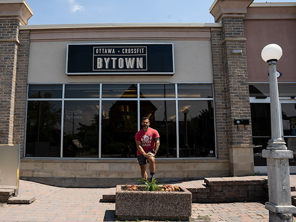 """A man in a red t-shirt stands in front of a gym building with a sign that reads """"Ottawa Crossfit Bytown""""."""