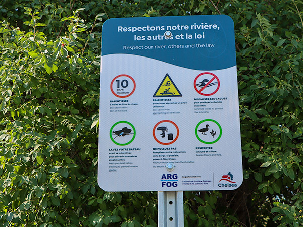 A sign informing boaters about speed limits to reduce wake and other rules for boating on the Gatineau River.