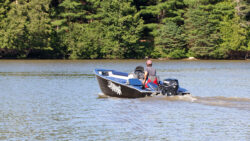 A fishing boat powers down the Gatineau Rivers.