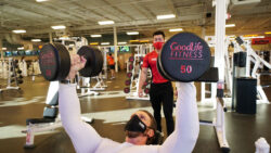 A man lifts two 50 pound dumbbells while a personal training watches from behind.