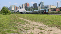 A grassy pathway running beside Ottawa's Confederation LRT line. A train pulls out of Pimisi Station.