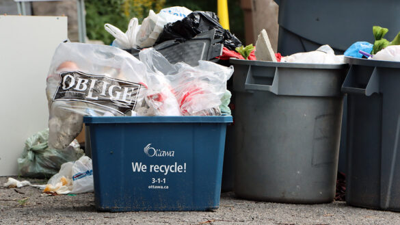 Over flowing garbage and recycling bins sit on the curb.