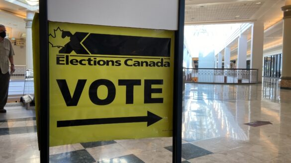 A yellow Elections Canada sign points voters to an advance polling station. Photo: Jonathan Got.