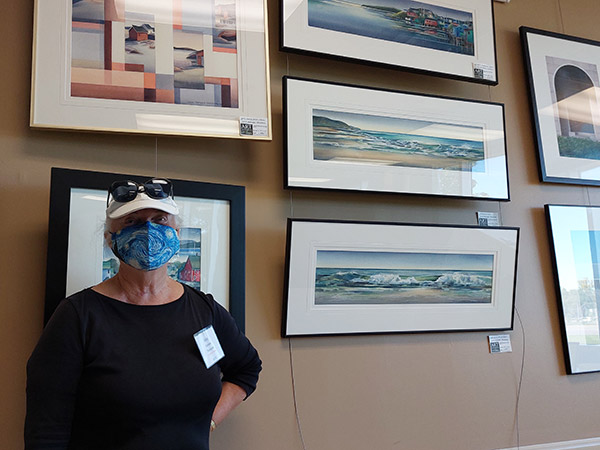 Anne Remmer Thompson stands in front of five watercolors.