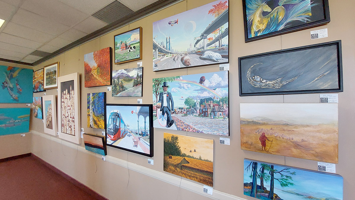 Paintings of different sizes hang on the wall.