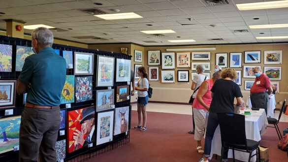 Guests look at paintings and photographs