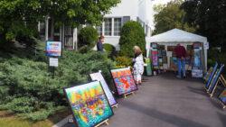 Art displayed in driveway, 2 visitors looking at art.