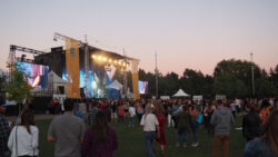 Crowd stands before the main stage at sunset.