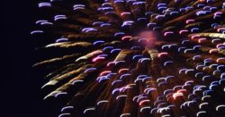 A long exposure shot of a firework exploding across the night sky in reds, blues and yellows.