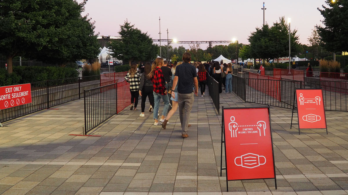 Attendees walk towards the entrance of an outdoor concert event, red signs displaying social distancing rules and mask mandates are in the forefront.