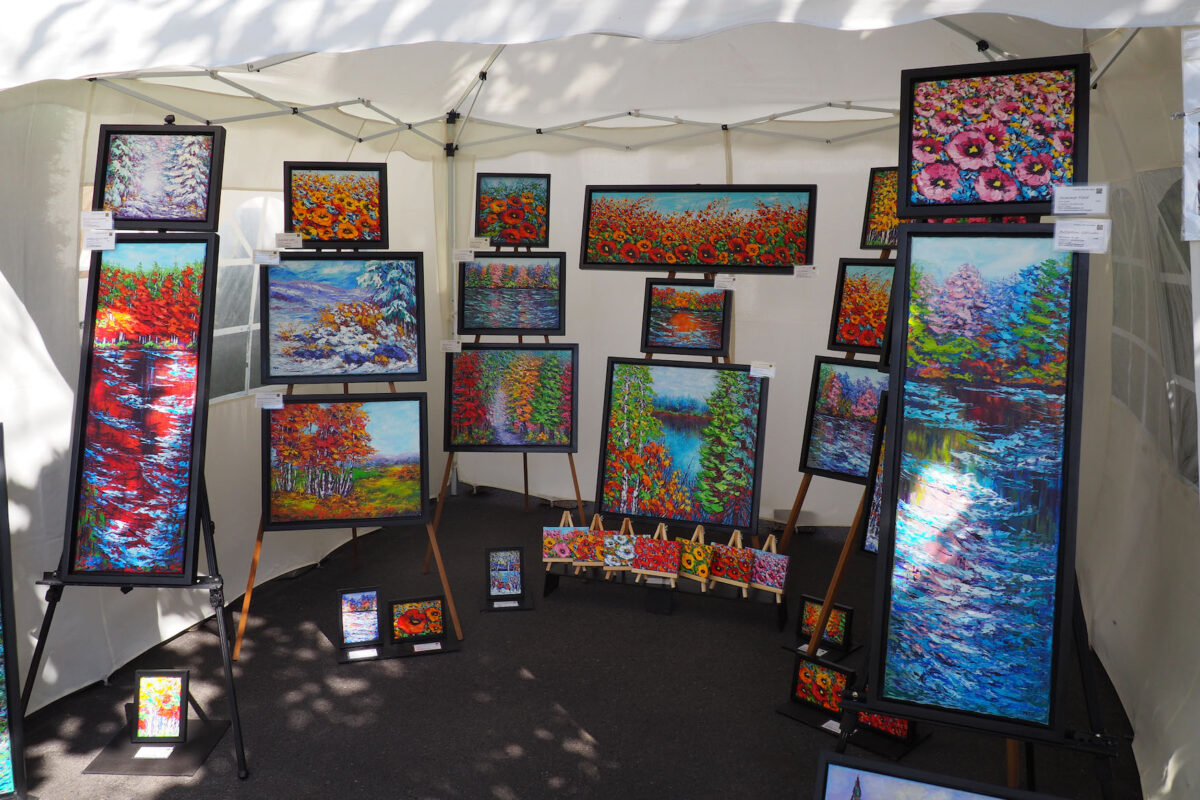 Vibrant and bright floral and landscape paintings displayed outside.