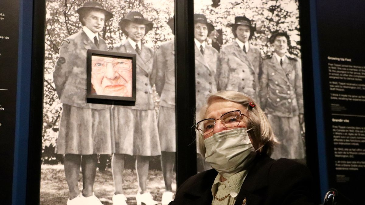An older woman in a wheelchair and mask sits in front of a painted portrait of her. Behind the portrait is a large-scale photo of a group of women in uniform during the Second World War.