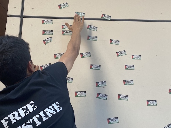 """Protestor leaving stickers of the Palestinian flag that read """"boycott Israeli apartheid"""" on a wall of the outside of the Israeli Embassy."""
