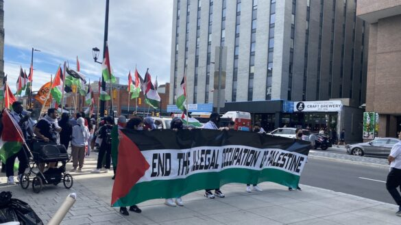 """Banner with the Palestinian flag that reads """"end the illegal occupation of Palestine"""" held ahead of a crowd carrying flags and other protests as they walk downtown in protest."""