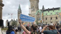 """Protestor holding a sign that says """"Climate action now. Action Climatique maintenant"""" with the Parliament in the background."""