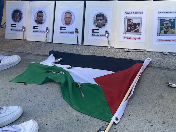 Printed out photos of escaped Palestinian prisoners on the ground, along with spoons and the Palestinian flag.