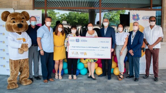 A large teddy bear, who is the CHEO mascott, stands with a group of nine people, who are presenting a giant cardboard cheque to the Roger Neilson House