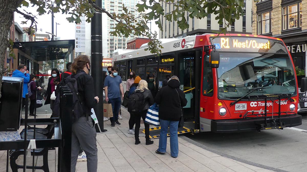 Citizens board an R1 bus on Rideau Street.