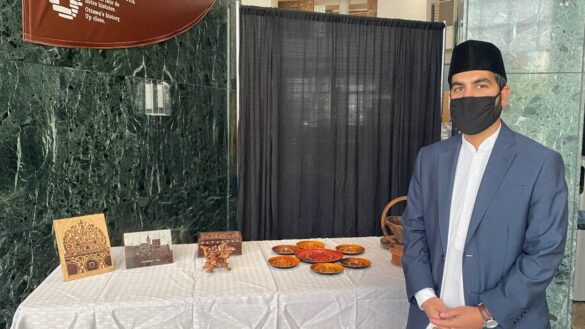 Sinwan Basharat standing to the right of a table. On the table is a white tablecloth, and pieces of Islamic geographic art and calligraphy, as well as artistic stamps for prints of mosques.