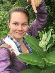Megan Reich stands outdoors pointing to the flower of a milkweed plant she is holding. The photo was taken during her trip across the eastern United States.