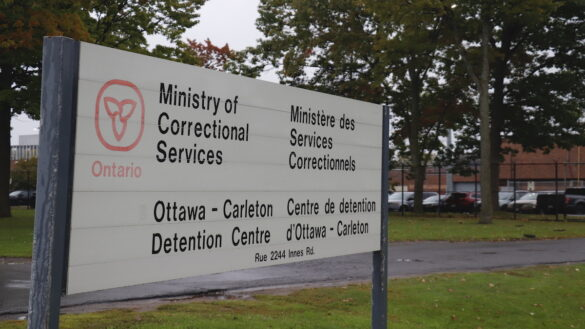 The sign in front of the Ottawa Carleton Detention Centre with the prison in the background