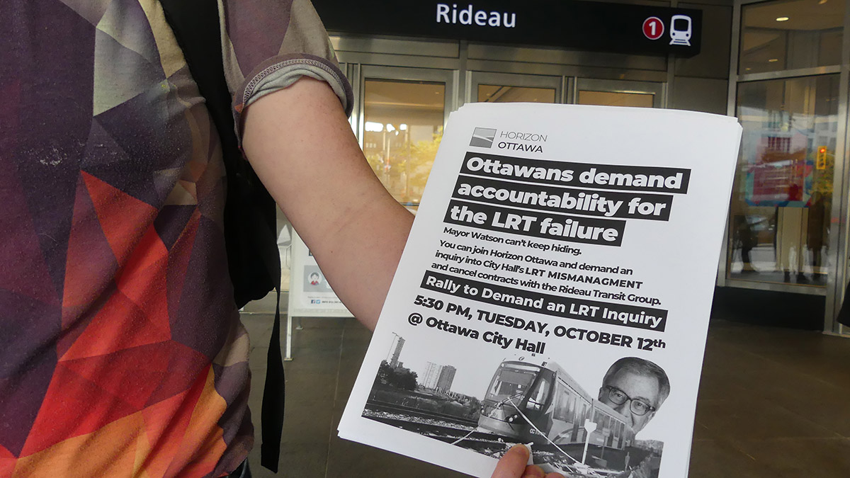 Sam Hersh, a board member with Horizon Ottawa, holds flyers of an upcoming rally.
