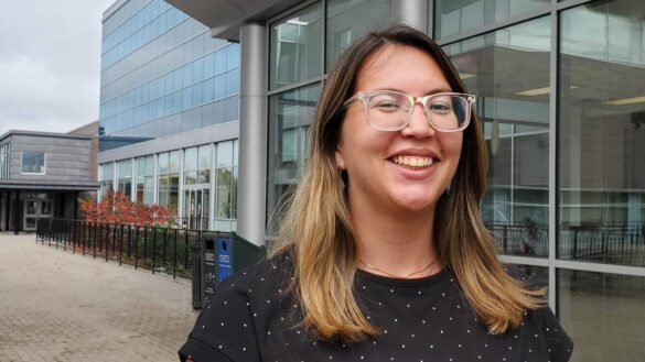 Pictured, Mariana Queiroz stands in front of Tory Building at Carleton University.