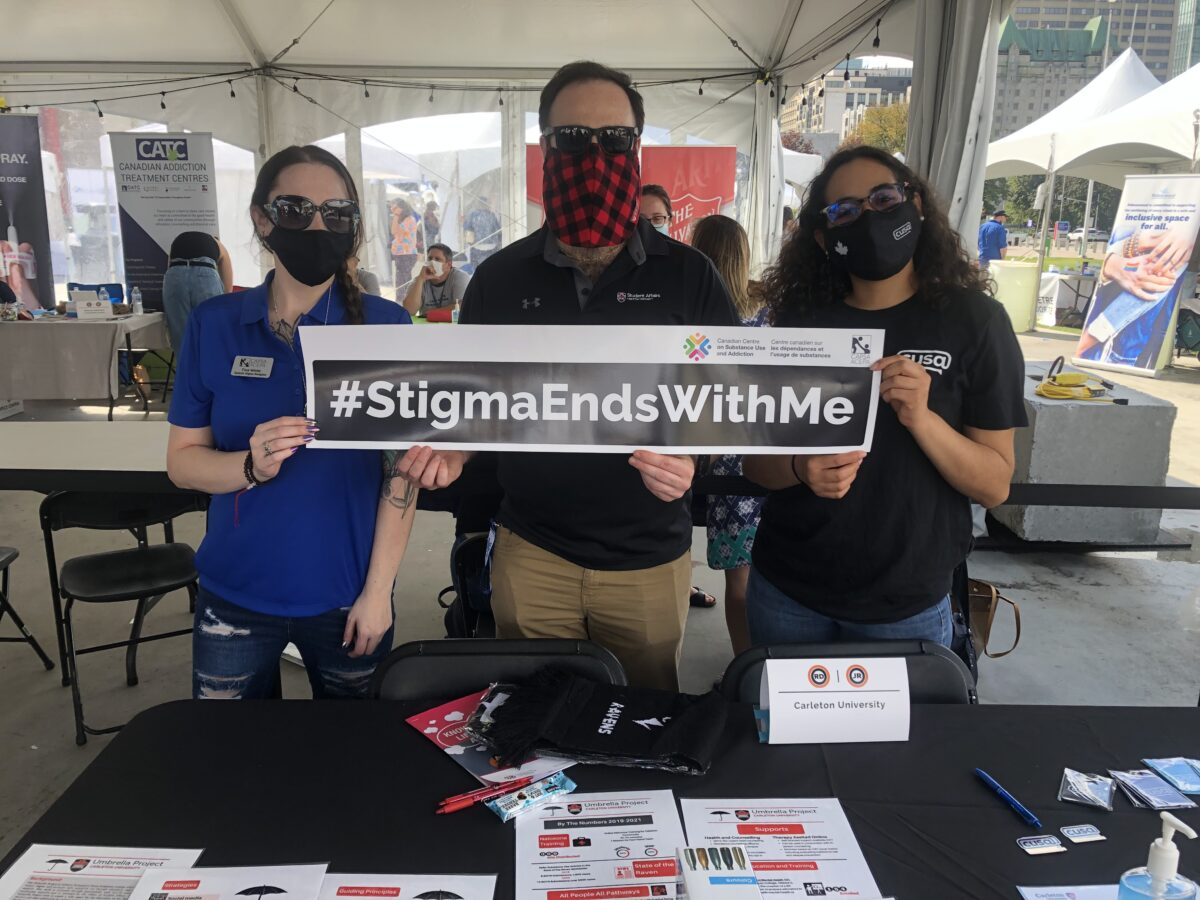"""Image shows three people holding """"stigma ends with me"""" banner at the Carleton University table outside of Ottawa City Hall."""