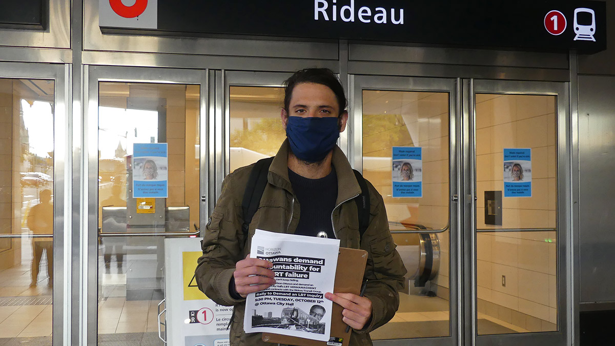 Sam Hersh, a board member with Horizon Ottawa, stands in front of the closed doors at Rideau station. He is wearing a blue mask and a green jacket while holding up flyers for an upcoming rally event.