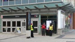 City officials wearing safety vests stand outside the closed doors of Rideau station.